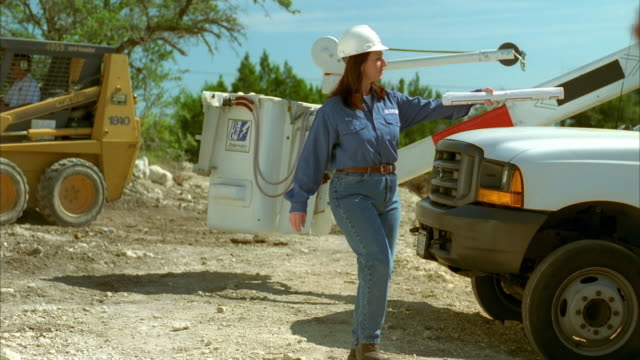 slo mo ms pan female lineman walking on construction site to talk with two male linemen / johnson city, texas, usa - see other clips from this shoot 1842 stock videos & royalty-free footage