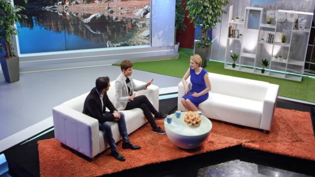 ospite di talk show dal vivo femminile che parla con la conduttrice femminile e l'ospite maschile - ospite video stock e b–roll