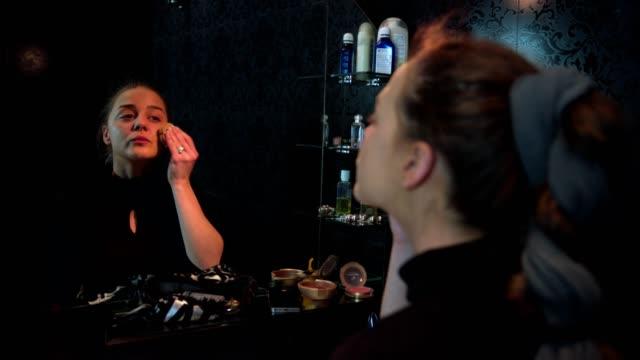 vidéos et rushes de femme regardant le miroir fait de son maquillage appliquer la fondation et souffle un baiser - pinceau à blush