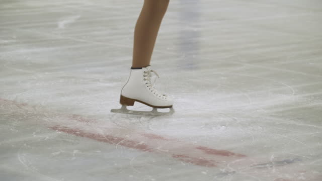 female, low section spinning round on ice skates on ice rink. - figure skating stock videos & royalty-free footage
