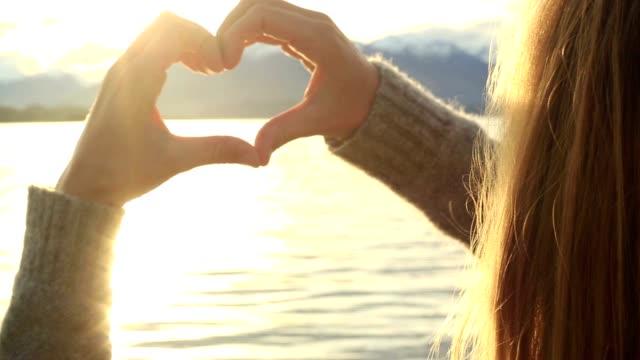 Female makes heart shape finger frame on lake mountain landscape