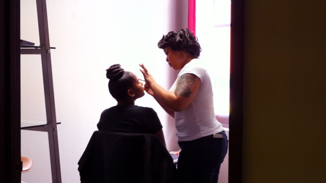 MS Female makeup artist applying makeup to client during makeover in salon