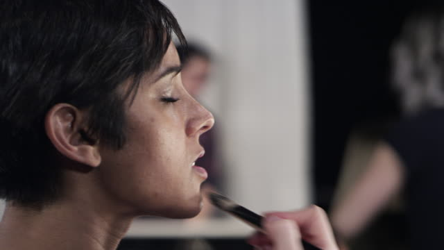 cu pan female makeup artist backstage at fashion show applying make-up  - メイクアップアーティスト点の映像素材/bロール