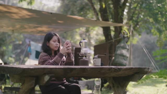 vídeos de stock, filmes e b-roll de mulher fazendo café usando a mão e tirando uma foto de sua cafeteira com um smartphone em viagem de acampamento. - antiguidade