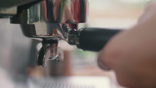 vidéos et rushes de femme faire du café avec la machine. - bar