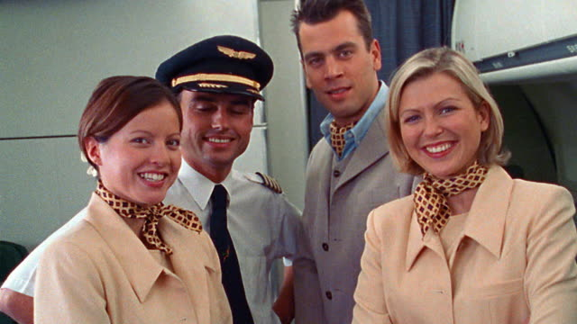 DSI PORTRAIT female + male flight attendants + pilot smiling + laughing standing in airliner