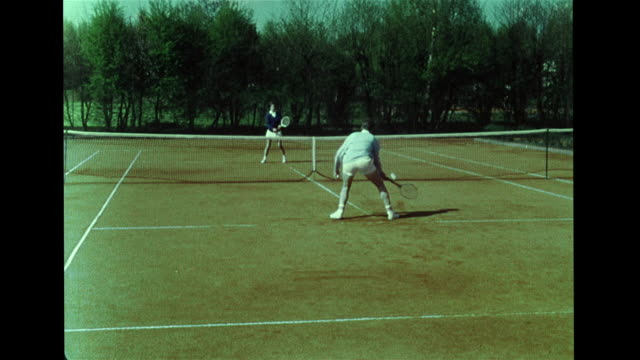 vídeos de stock e filmes b-roll de female & male playing tennis on grass court, hitting ball w/ racquets, reverse film: game play, girl walking backward off court. tennis couple in... - raqueta