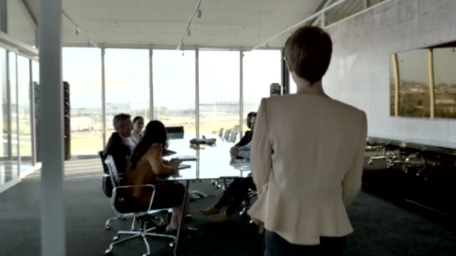 female manager discussing with team in board room - kurzes haar stock-videos und b-roll-filmmaterial