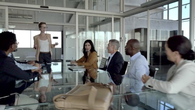 female manager discussing with team in office - dirigente video stock e b–roll