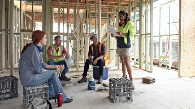 female manager giving instructions to her colleagues at construction site on the coffee break - safety stock videos & royalty-free footage