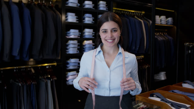 female manager of a men's clothing store smiling at camera holding a tape measure around her neck - cassiere video stock e b–roll