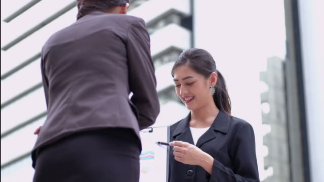 kvinnliga chefen presenterar nya projektplan till kollegor vid möte, förklarar idéer på fil. - formella kontorskläder bildbanksvideor och videomaterial från bakom kulisserna