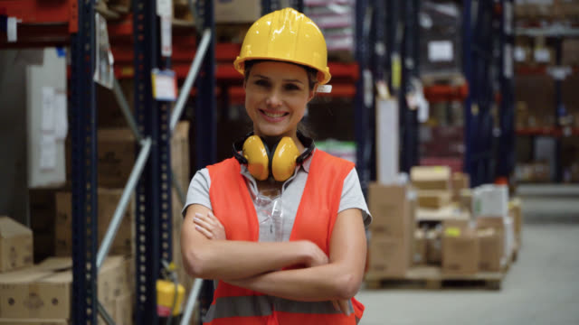 female manual worker working at a warehouse looking at camera smiling wearing protective workwear - world trade organisation stock videos & royalty-free footage