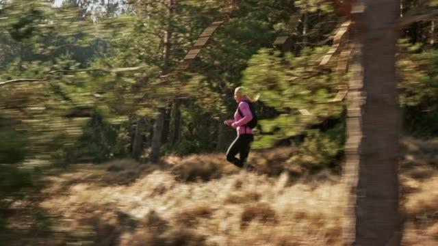 TS Female marathon runner running down a sunny trail along a forest