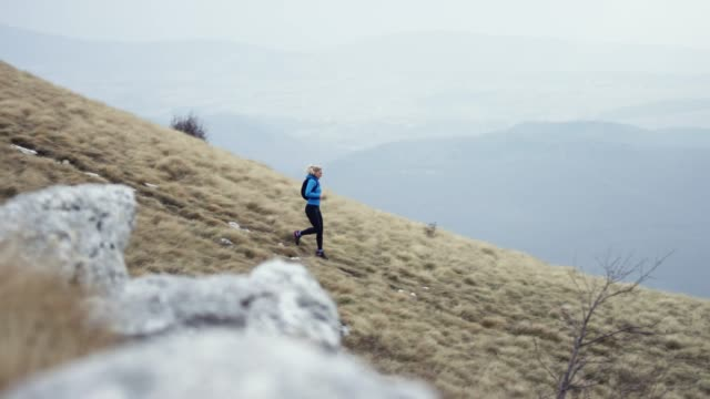 female marathon runner running down the grassy mountain slope in cloudy weather - 40 44 years stock videos & royalty-free footage
