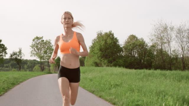 vídeos de stock, filmes e b-roll de slo mo t feminino maratona corredor correndo na estrada de asfalto - sutiã para esportes