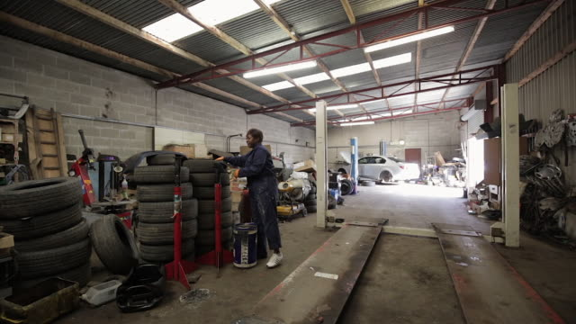 female mechanic carrying a tire in a garage - repair garage stock videos & royalty-free footage