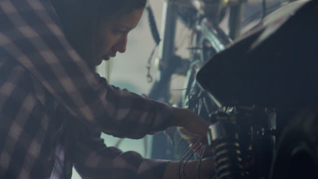 ms. female mechanic cuts motorcycle wires with cable and housing cutters. - riparare video stock e b–roll