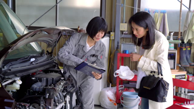 female mechanic explaining repairs to a customer - jumpsuit stock videos & royalty-free footage