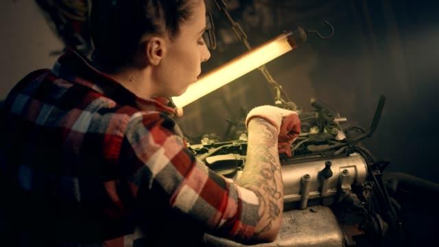 female mechanic in a workshop. fixing engine - repair garage stock videos & royalty-free footage