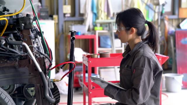 彼女のガレージの車に取り組んでいる女性メカニック - 労働者階級点の映像素材/bロール