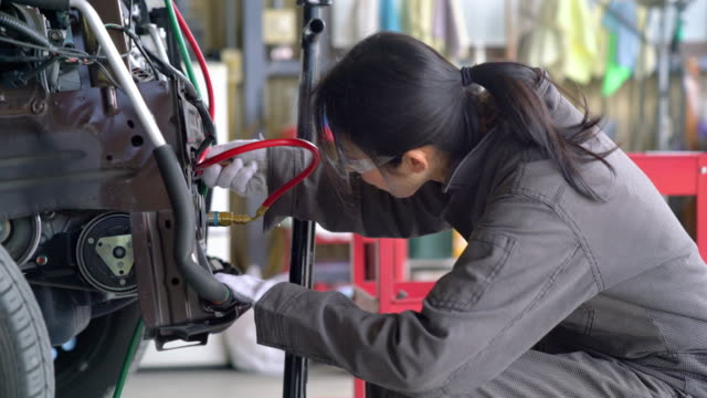 Female mechanic in her garage working on a car