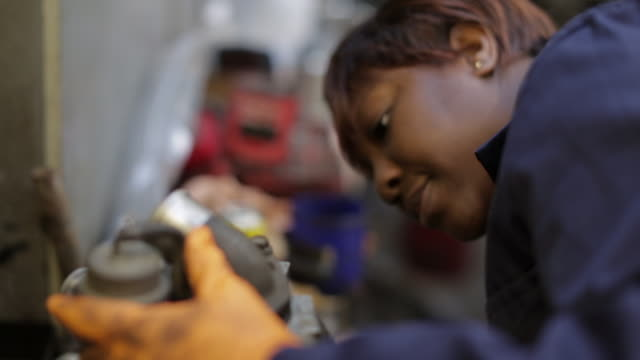 female mechanic inspecting part of an engine - manual worker stock videos & royalty-free footage