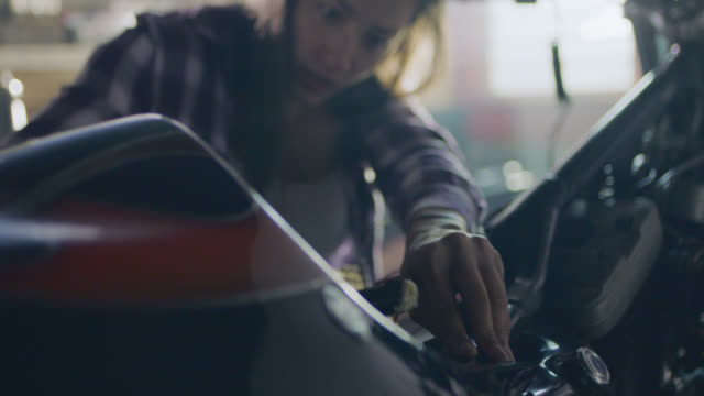 MS. Female mechanic rewires and polishes motorcycle in automotive repair shop.