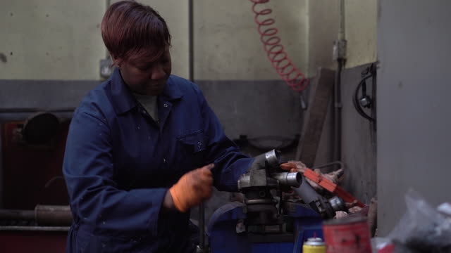 Female Mechanic Using a Vice to Hold an Engine Part