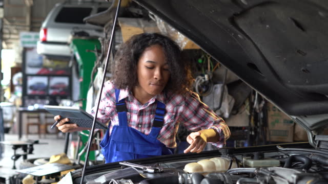 female mechanic working in her garage - dreiviertelansicht stock-videos und b-roll-filmmaterial