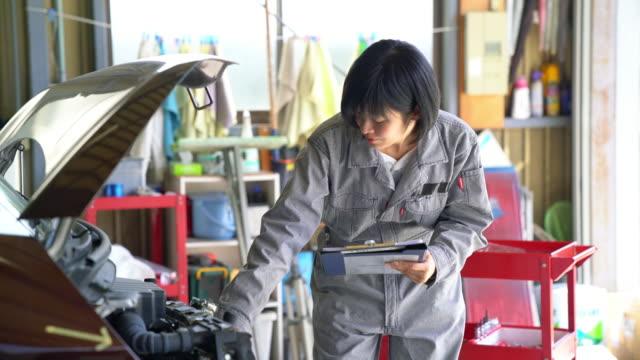 vidéos et rushes de mécanicien de femme travaillant dans son garage - examen