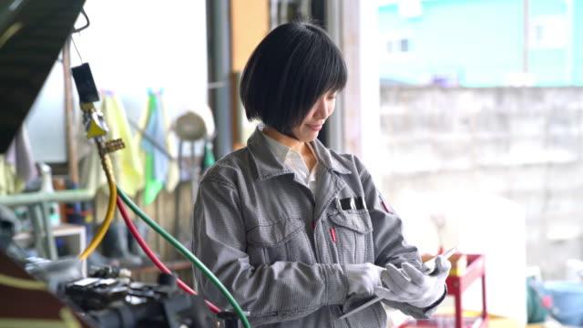 彼女のガレージで働く女性メカニック - 機械工点の映像素材/bロール