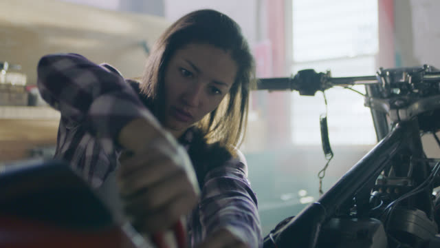 ms. female mechanic works on motorcycle wiring with cable and housing cutters. - mechanic stock videos and b-roll footage