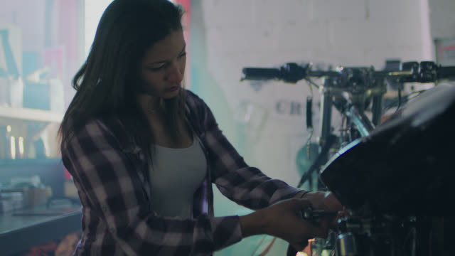 ms. female mechanic works on motorcycle with ratcheting socket wrench in automotive repair shop. - riparare video stock e b–roll
