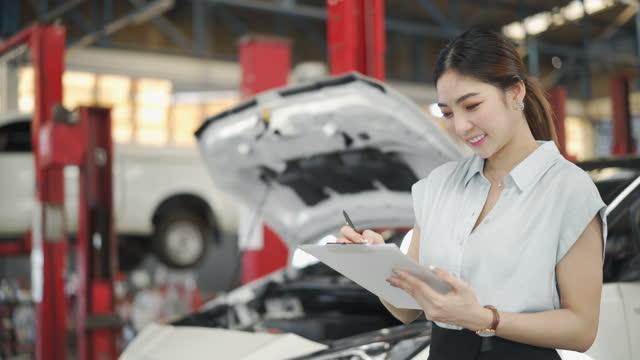 vidéos et rushes de 4k ingénieur mécanique féminin travaillant dans l'atelier de réparation automatique - partie de véhicule