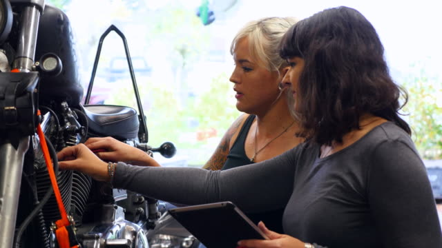 Female mechanics working on motorcycle in garage referencing manual on digital tablet