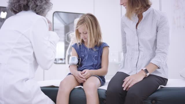vídeos de stock, filmes e b-roll de 4k uhd: pulso feminino tendo profissionais médicos de uma jovem garota - clínica médica