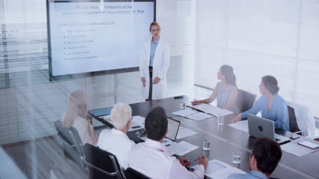 female medical researcher giving a presentation on a virus to a medical team - board room stock videos & royalty-free footage