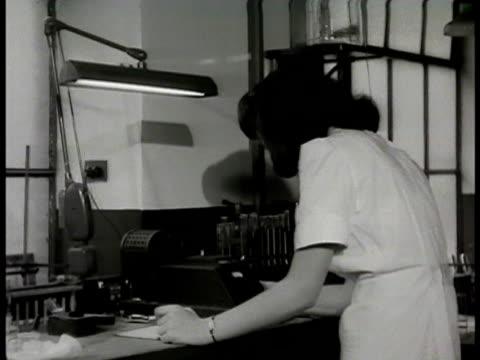 Female medical technician working w/ photoelectric colorimeter checking hemoglobin CU Dial on photoelectric colorimeter Modern medicine 1948 now...