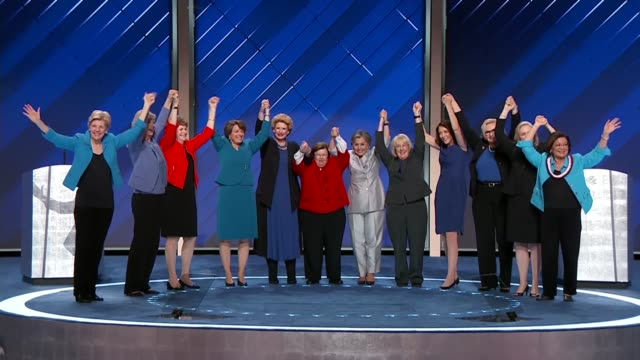 Female members of the Senate Democratic Caucus links arms and wave at the crowd before exiting the stage after speaking successively