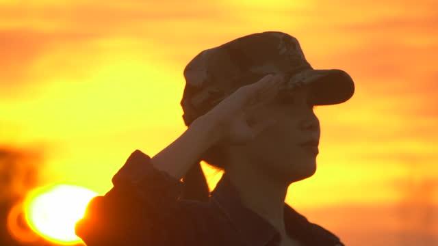 stockvideo's en b-roll-footage met vrouwelijke militaire silhouet militair salute in zonsondergang - salueren