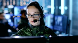 Female Military Technical Support Professional Gives Instructions into Headset. She's in a Monitoring Room with Other Officers and Many Working Displays.