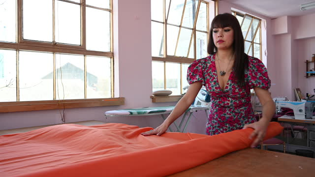 female mixed race designer unrolling bolt of orange fabric - workbench stock videos & royalty-free footage