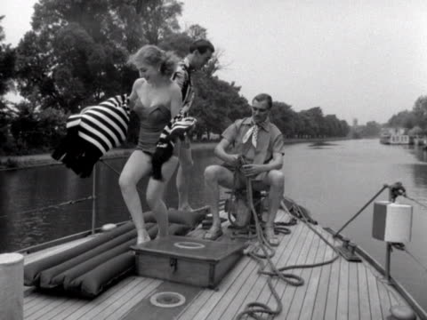 vidéos et rushes de a female model and two male models show off their swimwear and casual shirts on a boat moving along the river thames - châle