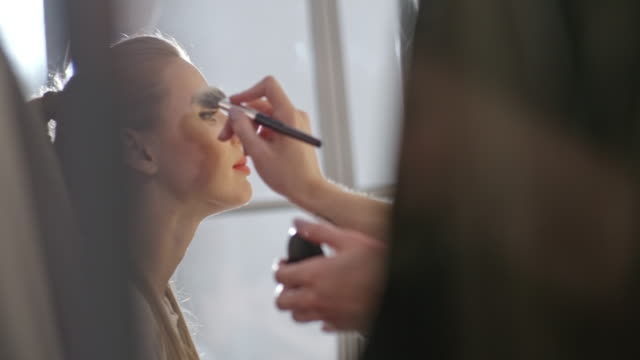 female model getting make-up done for photo shoot - beautician stock videos and b-roll footage