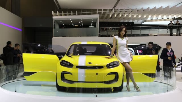 a female model stands by a kia motors corp cub concept vehicle which stands on display during the press day of the seoul motor show in goyang the... - goyang stock videos and b-roll footage