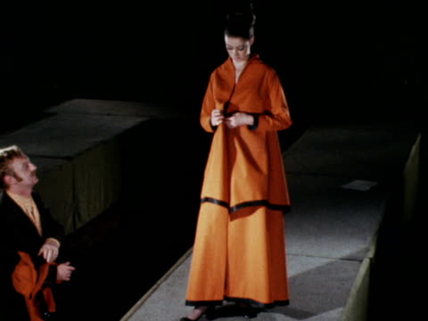 A female model takes off three sections of an orange coat to reveal an evening gown underneath 1970