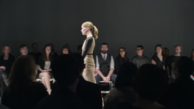 MS Female model walking alone on catwalk in front of crowd at fashion show