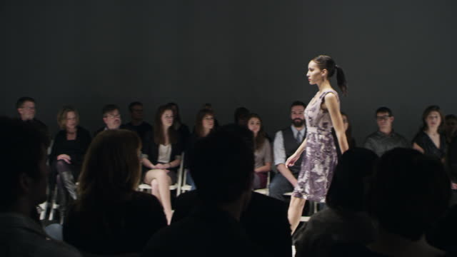ms female model walking alone on catwalk in front of crowd at fashion show - fashion model stock videos and b-roll footage