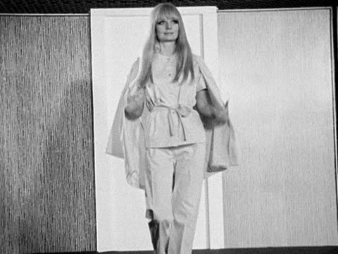 A female model walks down a catwalk wearing pyjamas and a jacket designed by Hardy Amies 1968 n